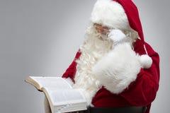 Santa has Faith. Santa Claus reading from the bible Royalty Free Stock Image