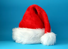 Santa hat. Red and white santa hat shot on a blue background Stock Photos