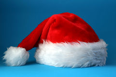 Santa hat. Red and white santa hat shot on a blue background Royalty Free Stock Photo