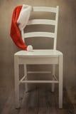 Santa Hat auf Stuhl über Retro- Hintergrund Weihnachtsfeiertagsfeier Stockfotos