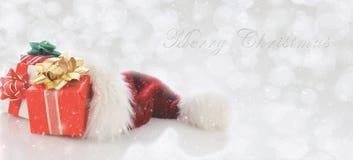 Santa Hat avec les présents et le type de Joyeux Noël photographie stock libre de droits