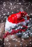 Santa hat ,  branches fur tree and red berries on aged  wooden b Royalty Free Stock Image
