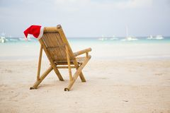 Santa hat on chaise longue on beach. Santa hat on chaise longue on white sand beach royalty free stock images