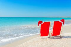 Santa hat on chaise longues at white sand beach against the sea Stock Images