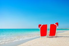 Santa hat on chaise longues at white sand beach against the sea Stock Photos
