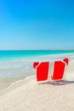 Santa hat on chaise longues at white sand beach against the sea Royalty Free Stock Photo
