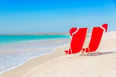 Santa hat on chaise longues at white sand beach against the sea Royalty Free Stock Images