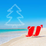 Santa hat on chaise longues at white sand beach against the sea. And clear sky with fir tree - christmas or new year holidays concept stock image