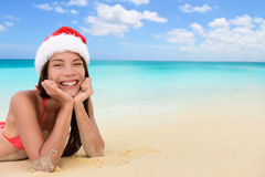 Santa hat Christmas Asian woman on tropical beach. Merry Christmas background concept for holiday season. Happy Asian woman on tropical beach in santa hat lying stock images