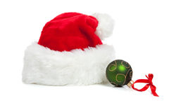 Santa hat and a Christmas ball on white Royalty Free Stock Photos