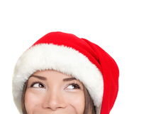 Santa hat christmas woman looking up. Closeup of beautiful christmas girl with smiling eyes looking at copy space isolated on white background Royalty Free Stock Image