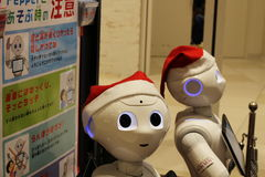 Santa-hat-clad Pepper robots in a Japanese shopping Mall Royalty Free Stock Images