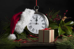 Santa Hat on Clock. A Santa Hat on a clock about to strike midnight, clock is surrounded by evergreen sprigs and magnolia leaves, a simple brown wrapped gift Stock Photography