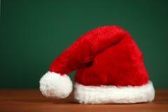 Santa Hat With Copy Space roja en fondo verde y de madera Foto de archivo libre de regalías