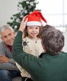 Santa Hat d'Adjusting Girl de père photos libres de droits