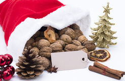 Santa hat with decoration. Santa hat filled with nuts and with decoration over white background stock photography