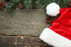 Santa hat with fir-tree branch. Red santa hat with fir-tree branch and cones on grey wooden table royalty free stock photography