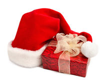 Santa hat and gift box on a white Royalty Free Stock Photos
