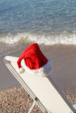 Santa Hat Hanging on Beach Chair. Royalty Free Stock Image