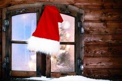Santa Hat Hanging an der rustikalen Fenster-Scheibe Stockfotos