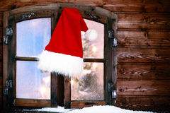 Santa Hat Hanging på det lantliga fönstret förser med rutor Arkivfoton