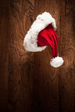 Santa hat hanging on a wooden surface Royalty Free Stock Photo
