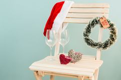 Santa hat, hearths and wine glasses royalty free stock photography