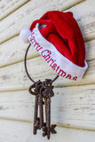 Santa hat and keys. Merry christmas santa hat and rustic keys hanging on a peeling painted weatherboard house royalty free stock images
