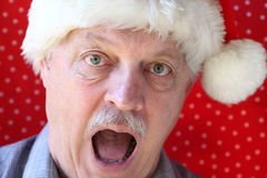 Santa hat on man looking alarmed Royalty Free Stock Photos