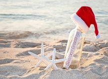 Santa hat on message in bottle with starfish stock photography