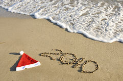 Santa hat with New Year on the sand. Royalty Free Stock Photo