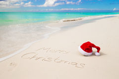Santa Hat no Sandy Beach e no Feliz Natal Fotos de Stock Royalty Free