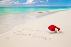 Santa Hat op zandig strand en Vrolijke Kerstmis Royalty-vrije Stock Foto's