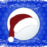 Santa Hat over festive blue background. Red and White Santa Hat Over Christmas Decorated Blue Background Royalty Free Stock Photography