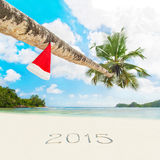 Santa hat on palm tree and 2015 year caption at sandy tropical b Stock Image