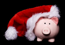 Santa hat piggy bank. Piggy bank wearing christmas santas hat cutout Royalty Free Stock Image