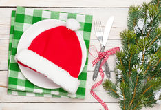 Santa hat on plate, silverware and christmas tree Royalty Free Stock Image
