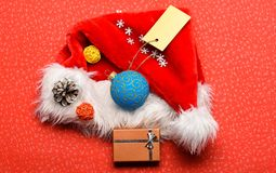 Santa hat red background top view. Santa hat with christmas gift box. Keep family traditions. Christmas presents from stock photos
