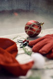 Santa hat, red gloves, holly and christmas ball. A santa hat, some twigs of pine tree and holly, a pair of cozy red gloves and a red and golden christmas ball on Royalty Free Stock Photography