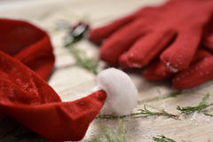 Santa hat, red gloves and holly. Closeup of a santa hat, a pair of cozy red gloves, some twigs of pine tree and a twig of holly in the background, on a rustic Royalty Free Stock Photography