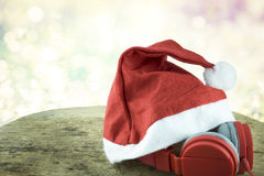 Santa hat and red headphone on woodden table over bokeh background. stock images