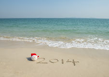 2014 with santa hat on sea beach sand Royalty Free Stock Image