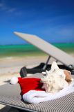 Santa Hat and seashell on chaise longue on beach. Santa Hat and seashell on chaise longue on caribbean beach royalty free stock images