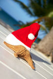 Santa hat and starfish on wooden table Royalty Free Stock Images
