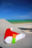 Santa Hat and sun tan on chaise longue. On caribbean beach stock photography