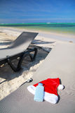 Santa Hat and sun tan on chaise longue. On tropical beach royalty free stock images