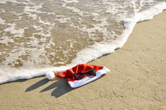 Santa hat and sunglass on thr sand. Royalty Free Stock Photo