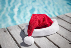 Santa hat by the swimming pool Royalty Free Stock Photos