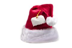 Santa hat with a tag. Isolated Santa hat with a blank tag attached Royalty Free Stock Images