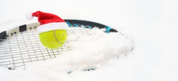 Santa hat on tennis ball on racket on white snow winter background with snowflakes. Merry Christmas and New year concept with stock image
